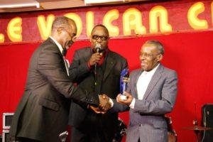 Pépé Félly qui remet à Luamba Mfumu Makanda Yves alias DEMUKUSE son trophée en 2013 lors de sa nomination dans la catégorie guitariste soliste de la nouvelle génération de la rumba congolaise moderne.